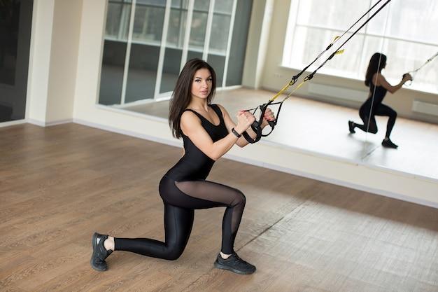Тренировочные упражнения молодой женщины нажимают вверх с ремнями фитнеса trx в тренажерном зале. концепция здорового образа жизни разминки.