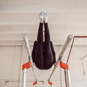 Тренировка молодой женщины для чемпионата по гимнастике