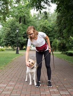 공원에서 개를 훈련시키는 젊은 여성