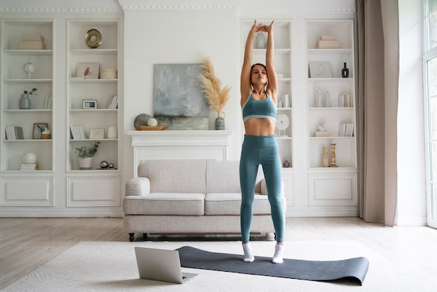 Young woman training at home alone