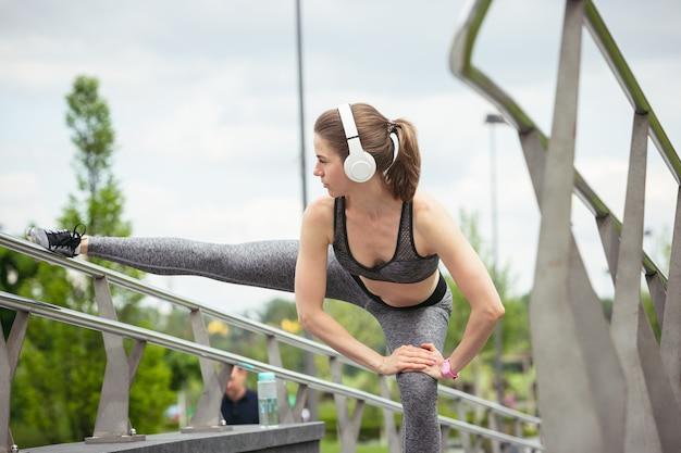 여름 시간에 공공 공원에서 훈련하는 젊은 여자 프리미엄 사진