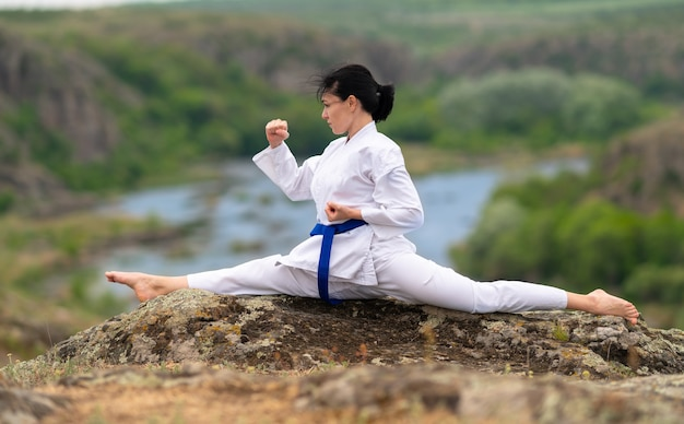 Young woman training for kickboxing doing the splits to increase her mobility