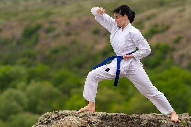 Young woman training for martial arts outdoors on a rock
