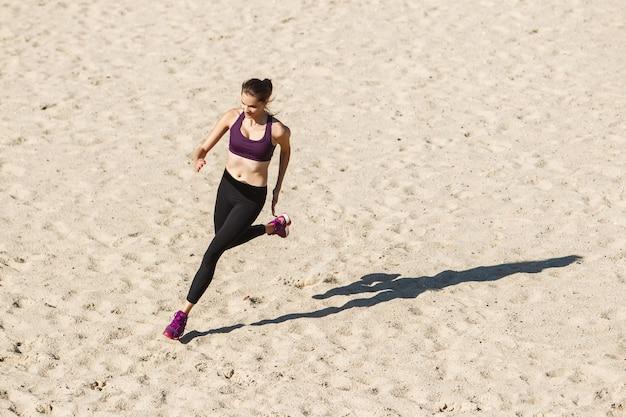 秋の日差しの中で屋外でトレーニングする若い女性。スポーツの概念、健康的なライフスタイル、