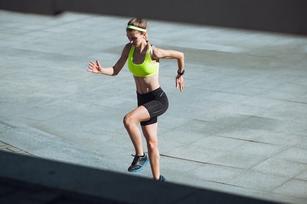 Тренировка молодой женщины на открытом воздухе в солнечном свете осени. концепция спорта, здорового образа жизни,