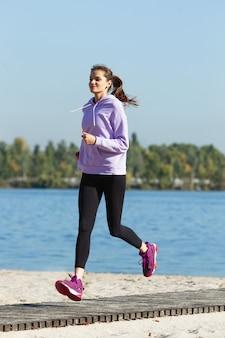 秋の日差しの中で屋外でトレーニングする若い女性。スポーツの概念