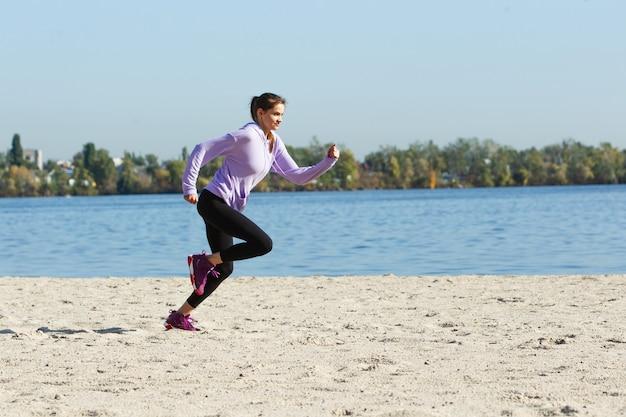 スポーツの秋の日差しの概念で屋外トレーニング若い女性