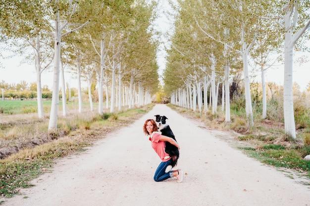 若い女性は木の道で彼女のかわいいボーダーコリー犬と屋外でトレーニングします。