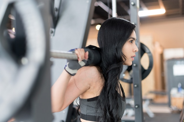 Young woman training with barbell in the gym