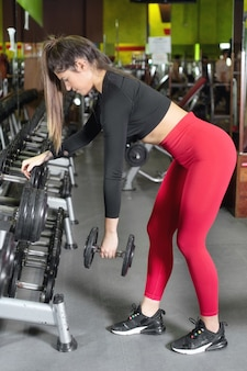 Young woman training with dumbbells in gym.