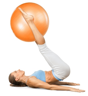 Young woman training with fitness ball on white background