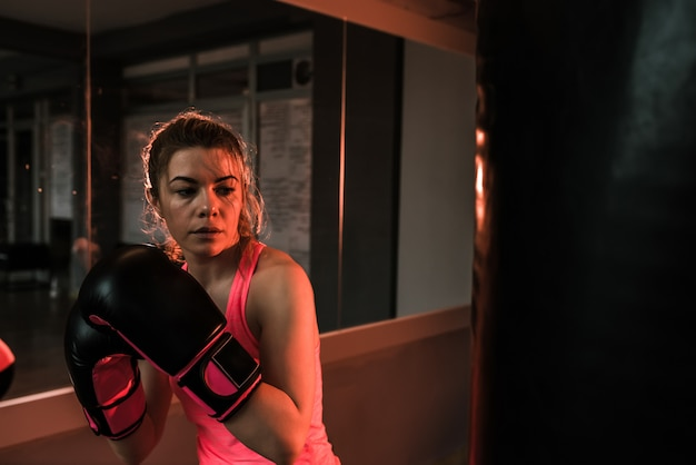 Young woman in training with heavy punching bag in gym. moment before punch.