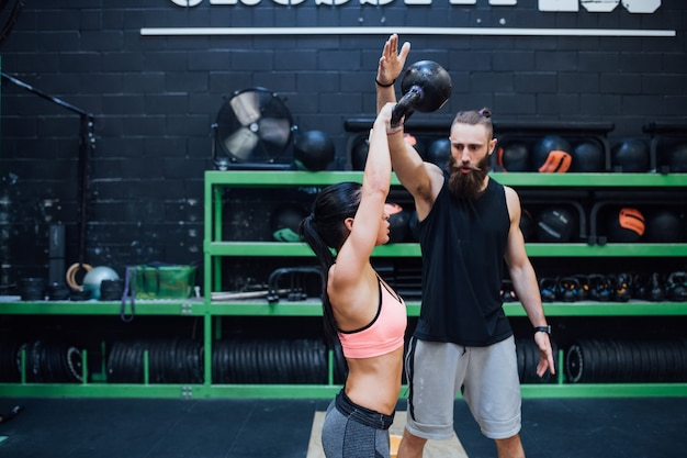 Young woman training with kettlebell helped by her personal trainer