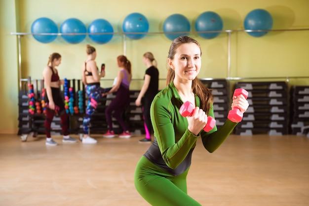 젊은 여자는 체육관에서 아령과 열차.