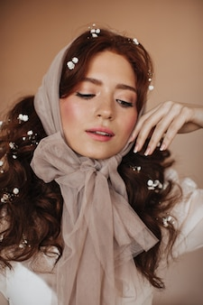 Young woman in transparent scarf on her head gently touches her face and modestly looks down.