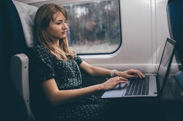 Путешествие молодой женщины в поезде. удаленная работа на ноутбуке во время сидения внутри. студенту или туристу предстоит небольшая поездка. бизнес. печатать на клавиатуре.