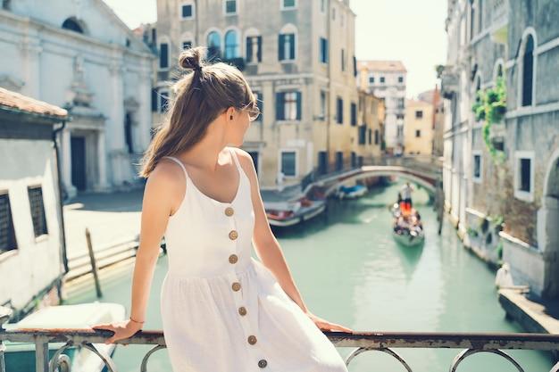 젊은 여성 여행 이탈리아 소녀는 베니스의 거리를 걷는 베니스 관광객의 아름다운 전망을 즐깁니다.