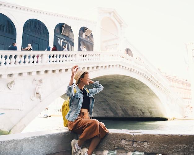 젊은 여성은 유럽에서 이탈리아 휴가를 여행하며 베네치아의 거리를 걷고 있는 소녀 관광객입니다.