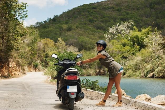 山の古い田舎道で若い女性旅行者とスクーター