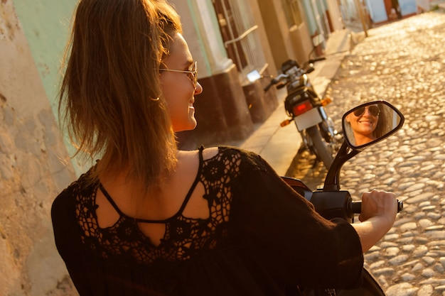旧市街の通りでスクーターを運転する若い女性旅行者