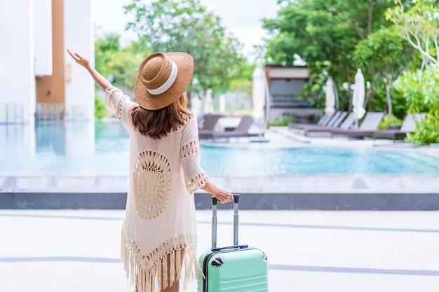 Молодая женщина-путешественница, наслаждающаяся летними каникулами в бассейне на тропическом курорте недалеко от пляжа