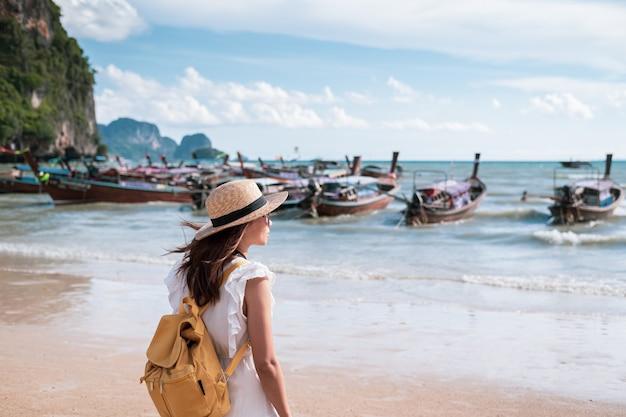 Young woman traveler enjoying a summer vacation at tropical sand beach in krabi, thailand