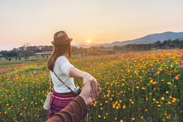 Young woman traveler holding man's hand and leading him on flowers field
