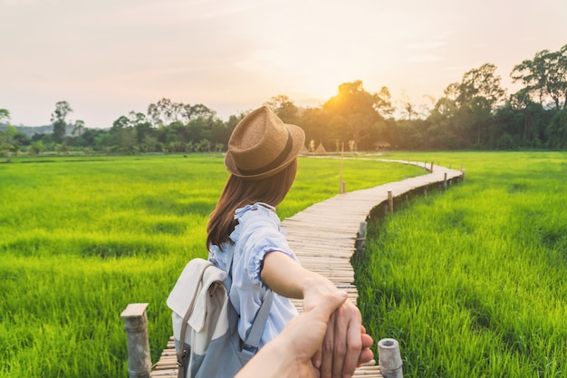 Young woman traveler holding man's hand and leading him on green paddy field