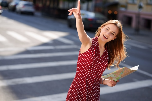 Young woman traveler holding paper map of the city and calling someone on the street in summer