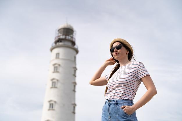 灯台を背景にポーズをとるサングラスと麦わら帽子の若い女性旅行者。海外旅行。海で休む。