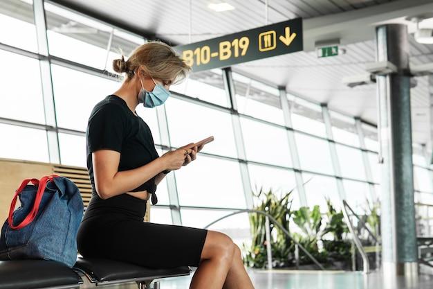 若い女性の旅行者は、飛行中の空港での着用防止マスクを待っています