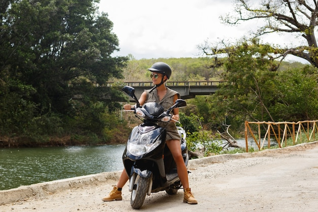 Young woman traveler is driving scooter on old rural road in the mountains