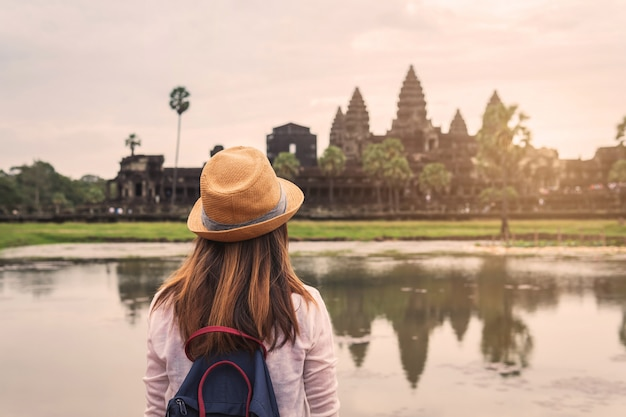 Young woman traveler looking at angkor wat, khmer architecture heritage