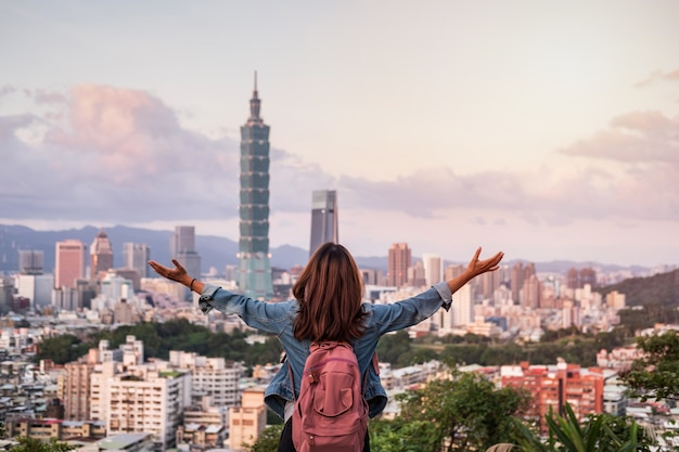Young woman traveler looking beautiful cityscape at sunset in taipei