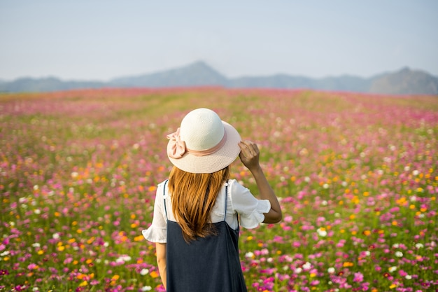 Young woman traveler  looking beautiful flowers field
