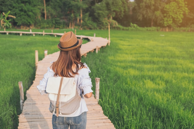 Young woman traveler looking at beautiful green paddy field