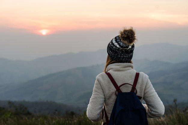 Young woman traveler looking at sunrise