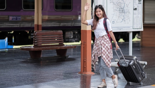 Young  woman traveler millennial waving hand, say hi, carrying her black suitcase on empty modern bus or tram stop.