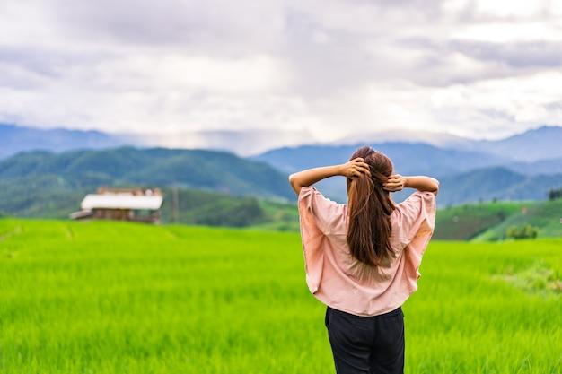 美しい緑の棚田フィールドを楽しんで見て休暇中の若い女性旅行者