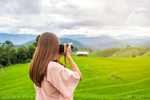 タイの美しい緑の棚田フィールドで写真を撮る休暇中の若い女性旅行者