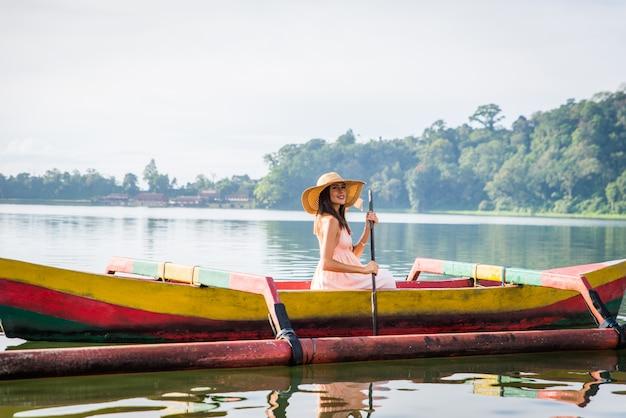 Young woman traveler paddling on a wooden boat at pura ulun danu bratan
