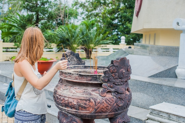 Young woman traveler praying in polite action with incense sticks at buddhism temple in vietnam
