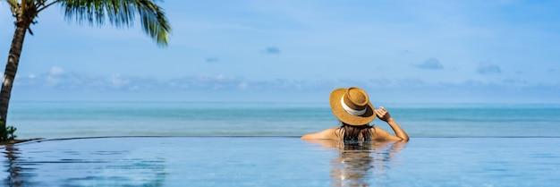 젊은 여자 여행자는 휴식과 여름 휴가를 위해 여행하는 동안 열대 리조트 수영장에서 즐기는 여행 개념