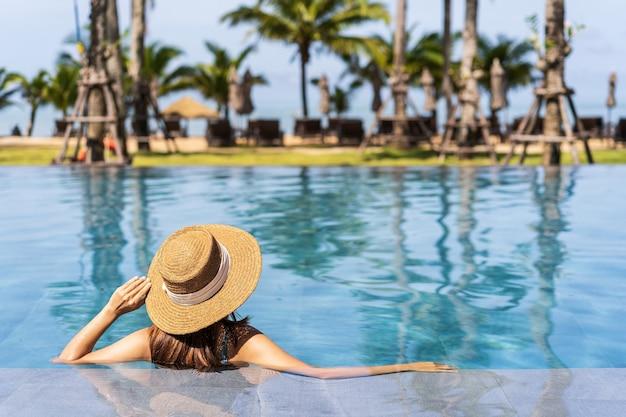 夏休み旅行中にトロピカルリゾートプールでリラックスして楽しむ若い女性旅行者、旅行のコンセプト
