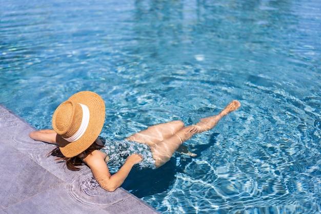 편안한 열대 리조트 수영장에서 즐기는 젊은 여성 여행자