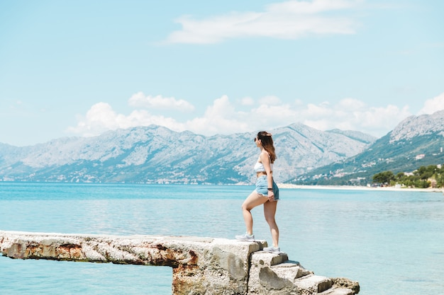 Young woman traveler in short jeans shorts walking along the ocean with mountains