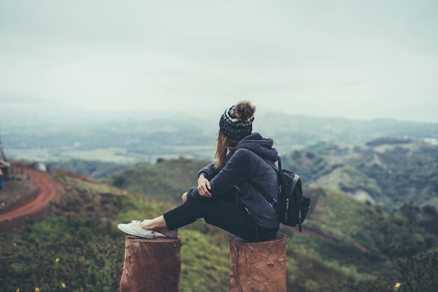 Young woman traveler sitting and looking view of nature