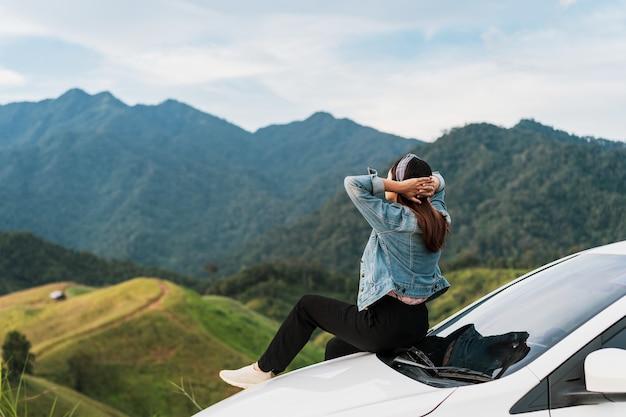 Молодая женщина-путешественница сидит в машине и смотрит красивый вид на горы, путешествуя по дороге в отпуск