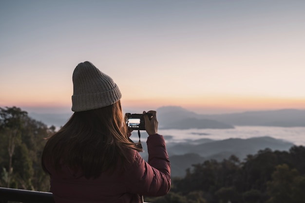 Young woman traveler taking a picture of beautiful landscape