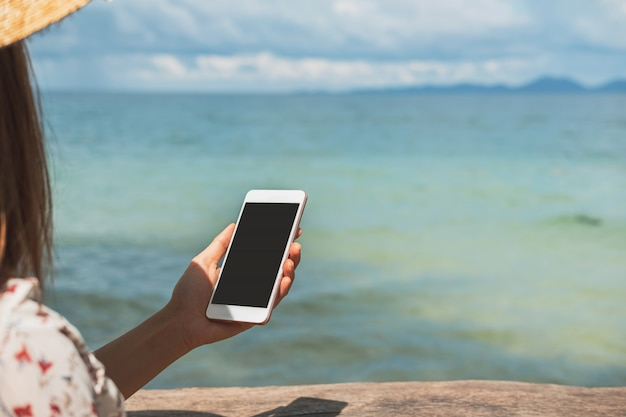 Young woman traveler using her smartphone at tropical sand beach, summer vacation